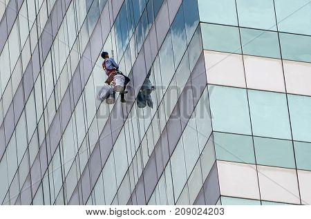 Asian Man Cleaning Window Service On High Rise Building