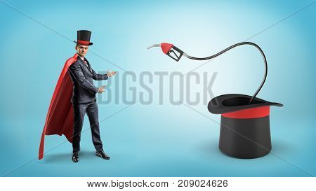 A businessman wearing a red cape and a big illusionist's hat shows a fuel nozzle inside a large magician's hat. Introduction in oil business. Commodities trade. Market consultant.