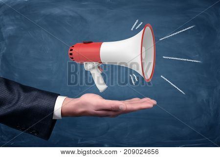 A businessman's arm with one hand held palm up and a working white and red megaphone standing on it. Public event. Spread news. Share information.