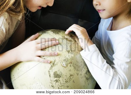 Little girls playing with a globe