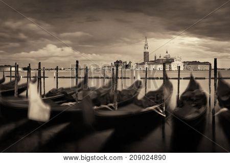 Gondola park in water and San Giorgio Maggiore island in Venice in an overcast day, Italy.