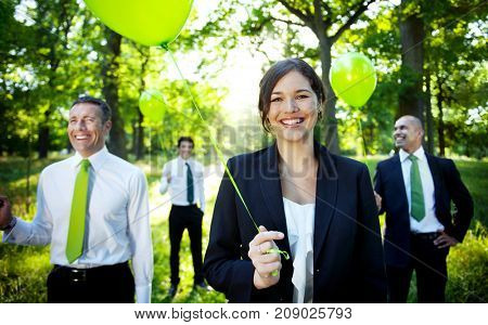 Business people holding green balloon in forest.