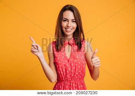 Smiling brunette woman in dress pointing up and showing thumb up while looking at the camera over yellow background
