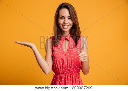 Smiling brunette woman in dress holing copyspace and showing thumb up while looking at the camera over yellow background