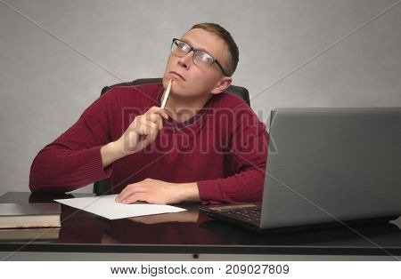 A thinking young student sits at desk table and pensive looks at the ceiling. Wistful business man with pen in the hand.