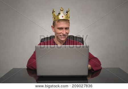 VIP client. Premium user. Success. Smiling happy Business man with golden crown above his head working with laptop computer. Top manager. Best employee.