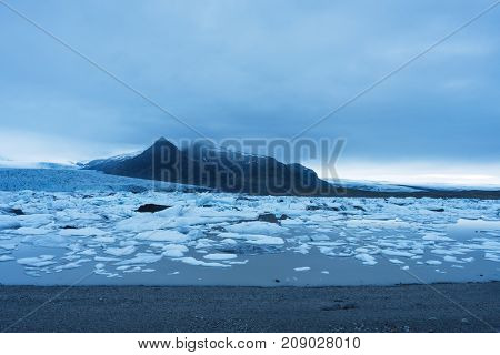 Evening landscape with ice floes in the glacial lake Fjallsarlon. Vatnajokull National Park, Iceland, Europe. Amazing tourist attraction
