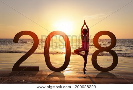 Happy new year card 2018. Silhouette of A girl doing Yoga vrikshasana tree pose on tropical beach with sunset sky background watching the sunset standing as a part of the Number 2018 sign.
