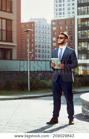 Real estate agent with tablet computer stands on modern city backdrop. Businessman or business concept