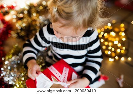 Cute little girl opening Christmas present. Close up.