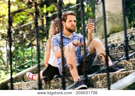 Beautiful young couple with smart phones sitting on stairs in old town, watching or reading something. Sunny spring day.