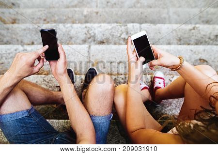 Unrecogizable young couple with smart phones sitting on stairs in town, texting. Sunny spring day.