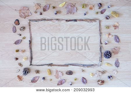 Autumn composition. Square frame made of dry sticks with dried leaves pine cones and dried fruits around. Flat lay top view copy space area available. On a wooden background