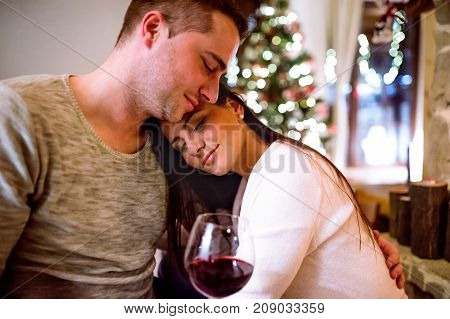 Beautiful young couple sitting on the floor in front of fireplace, drinking red wine. Christmas time.
