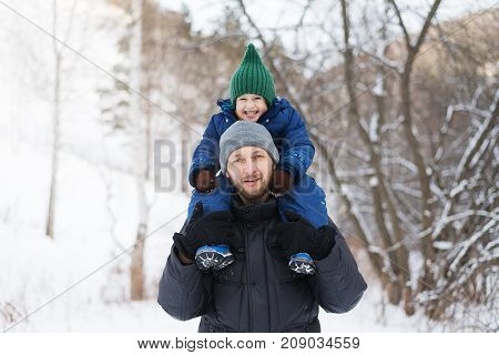 Father and child in a winter forest. The child is sitting on the fathers' shoulders. Shot with soft focus.