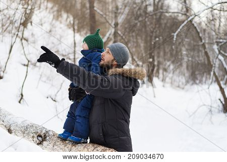 Father and child in a winter forest. Shot with soft focus. Child standing on a fallen tree. Father is pointing somewhere.