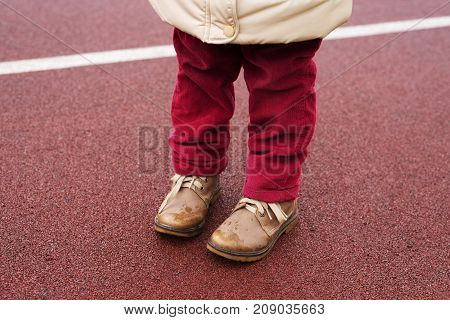 Little girl's legs in red velvet jeans and brown boots standing on a race track.