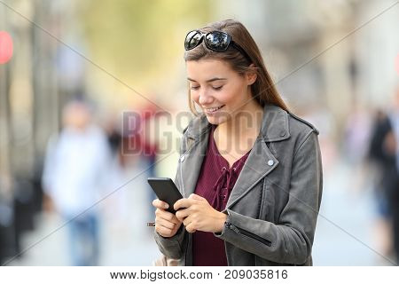 Fashion Girl Standing Using A Smart Phone On The Street