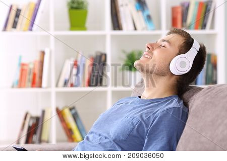 Side view portrait of a man relaxing sitting on a couch at home listening to music wearing headphones