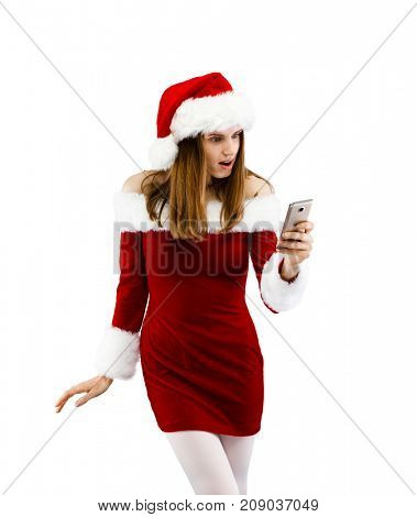 Beautiful woman in Santa Claus clothes using smartphone on white background