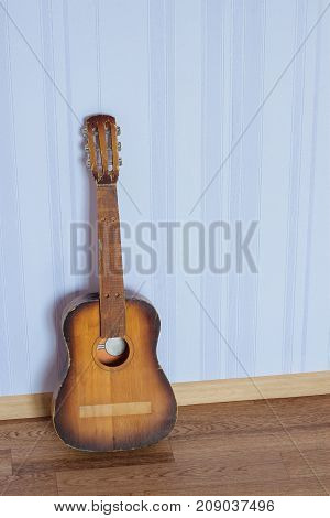 One old broken guitar of a small child size standing by the wall on the floor in the room. It has no strings, bridge and position makes.