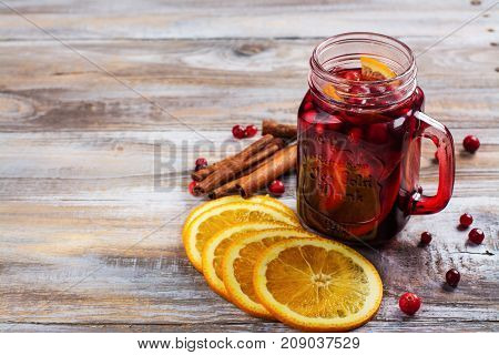 Cranberry and orange summer sangria with cranberry and oranges on wooden background. Copy space