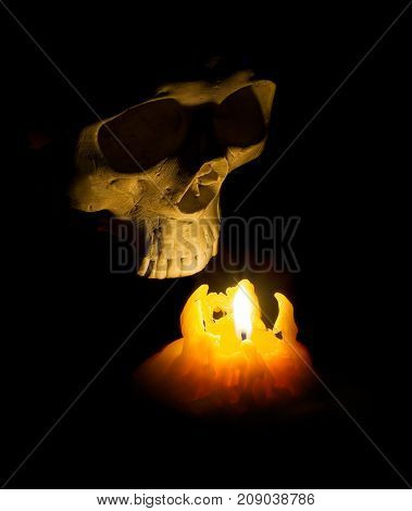 Halloween Ghost Human Skull Comes Out Of Darkness Lit With Candle.