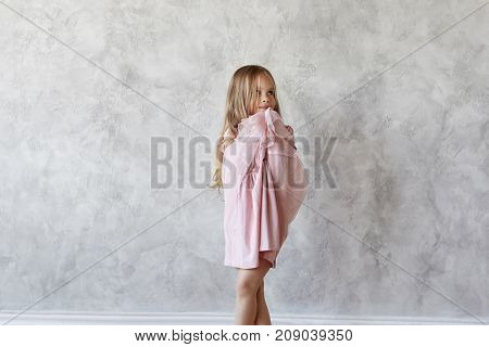 Adorable cute baby girl with long straight hair posing at blank grey wall wearing beautiful pink dress having shy look. Sweet female kid trying on fancy dress. Kids fashion and style concept