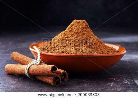 Ground cinnamon cinnamon sticks tied with jute rope and cinnamon powder in rustic style.