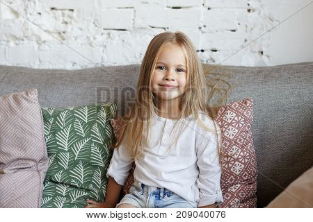 Positive beautiful little girl of European appearance sitting on comfortable sofa in living room surrounded with decorative pillows looking at camera and smiling happily. Childhood concept