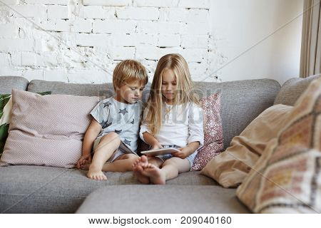 Two siblings using digital tablet together sitting on couch in living room watching cartoons online via social media. Little boy watching his elder sister playing video games on touch pad computer