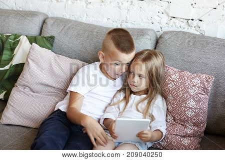 Scoolboy in white t-shirt and jeans sitting on couch teasing his little sister who is watching video blog online on touch pad. Elder brother trying to snatch electronic gadget from his sister's hands