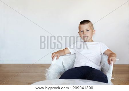 Picture of handsome blue eyed schoolboy with stylish haircut sitting in white chair in his room in confident posture thinking that he is special and unique his look expressing arrogance and conceit
