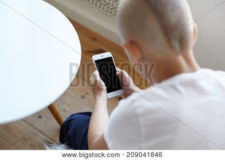 Back view of unrecognizable little boy using online photo editing application on smart phone while posting pictures via social networks sitting in home interior. Selective focus on hands wih gadget