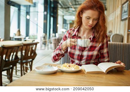 Young  beautiful woman in glasses reading interesting book in cafe