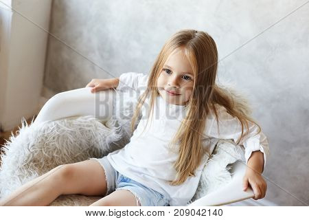 Indoor shot of charming blue eyed Caucasian little girl wearing her long straight hair loose sitting in relaxed posture on armachair at home and listening to her mother with attentive positive smile