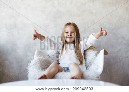 Portrait of charming happy little girl with bare feet and long straight hair sitting on white armchair showing thumbs up with both hands as sign of approving and liking good idea. Body language