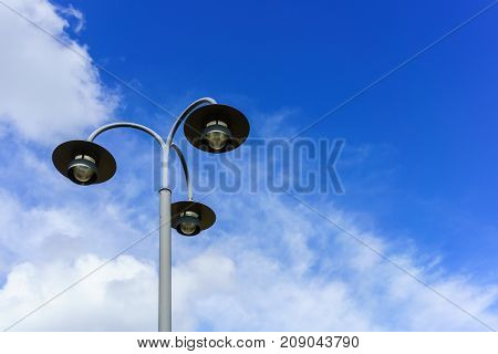 Street light or street lamp with white clouds and blue sky in France
