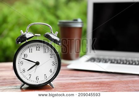 Clock alarm on wooden table outdoors. Morning routine concept