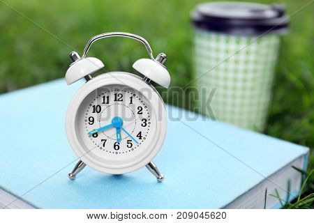 Alarm clock and book on green grass. Morning routine concept