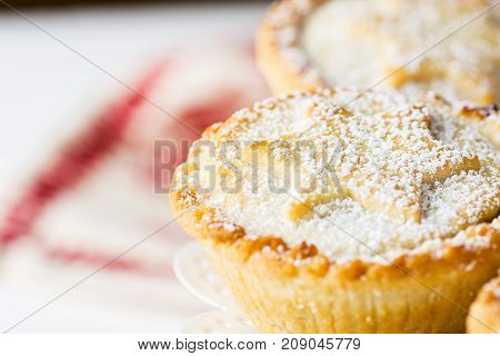 Traditional British Christmas Pastry Dessert Home Baked Mince Pies with Apple Raisins Nuts Filling on White Elegant Cake Stand. Golden Shortcrust Powdered. Festive Table Setting