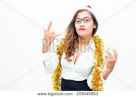 Portrait of confident young Asian businesswoman wearing Santa hat, glasses and tinsel holding champagne flute and showing horn gesture. Christmas and office party concept