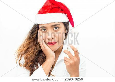 Face of confident young Asian businesswoman wearing Santa hat holding champagne flute and looking at camera. Christmas and office party concept