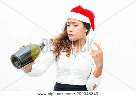 Portrait of young Asian businesswoman wearing Santa hat holding champagne flute and looking at bottle. Office Christmas and alcoholism concept