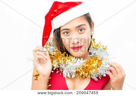 Portrait of positive young Asian woman wearing red dress and tinsel, touching Santa hat on her head, looking at camera and smiling. Christmas and New Year concept