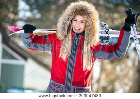 Happy woman with skis and poles on winter holiday