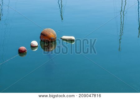 Colored buoys floating in port of Malta for mooring of yachts. Reflection of masts in calm water