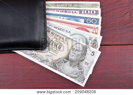 Mexican Pesos in the black wallet on a wooden background
