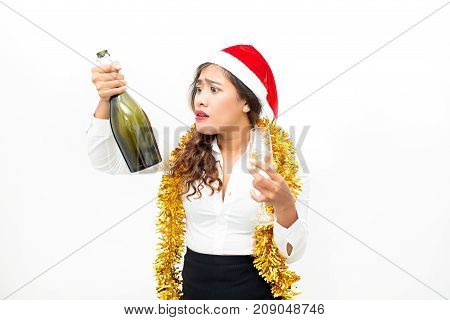 Portrait of upset young Asian businesswoman wearing Santa hat and tinsel holding champagne flute and looking at empty bottle. Christmas and alcoholism concept