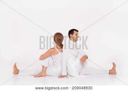 A man and a woman are sitting in a yoga pose. Yoga class paired with the coach.